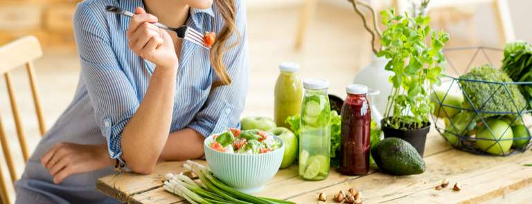 woman eating vegetables and salad at table