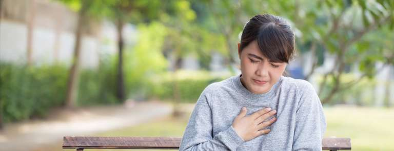 woman experiencing acid reflux on park bench