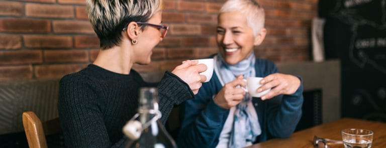 Senior mother sitting in cafe bar or restauant with her middle age daughter and enjoying in conversation.