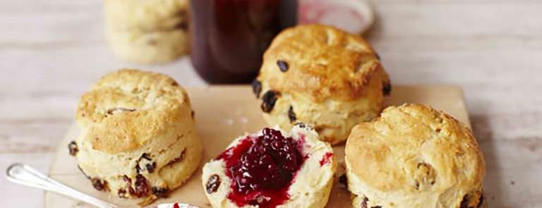 Fruit scones on a wooden chopping board with blackberry jam