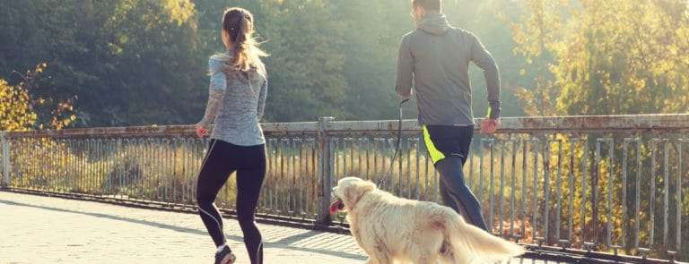 close up of couple with dog running outdoors