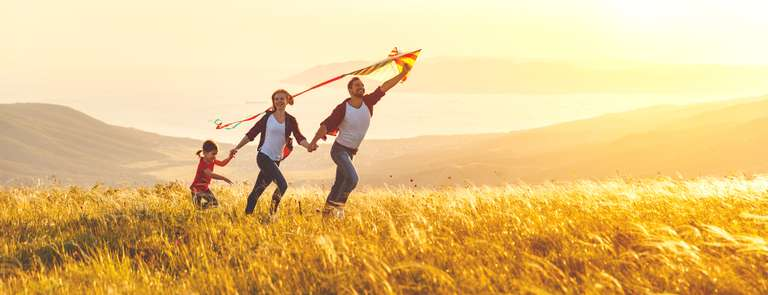 a family running through a field with a kite