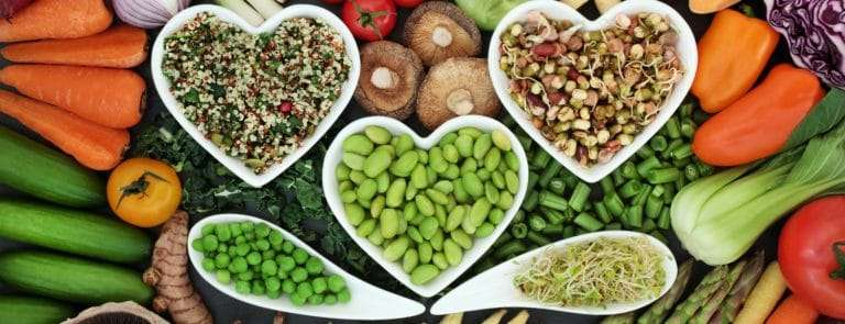 fresh vegetables loose and in heart shaped and curved bowls with food high in antioxidants, anthocyanins, vitamins, minerals and dietary fiber.