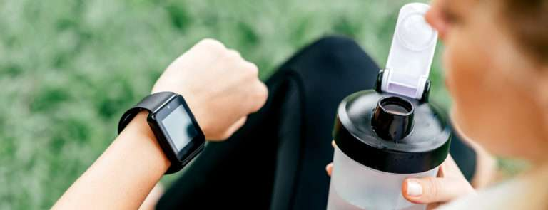 A lady checking her sports watch whilst having a shaker cup in her right hand.