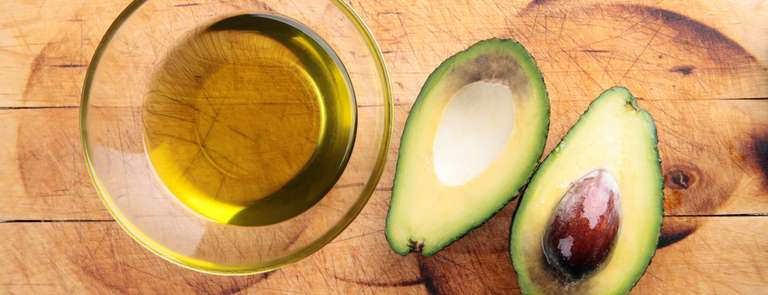 avocados with oil on a wooden surface