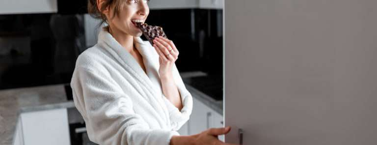 A lady eating dark chocolate whilst looking in her fridge.
