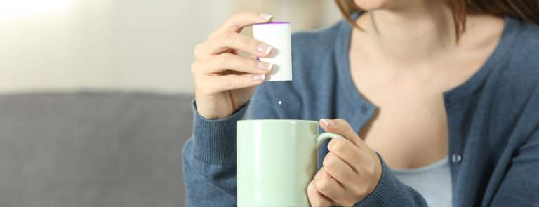 woman adding a sweetner to her hot drink