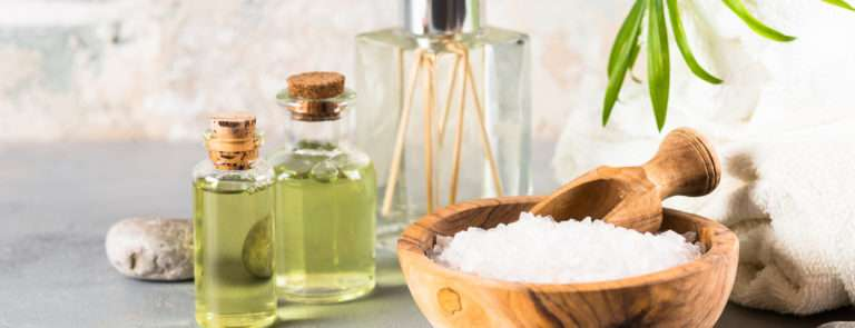 A reed diffuser, with a bowl of salt and a few jars of olive oil on a table. With some additional pebbles.