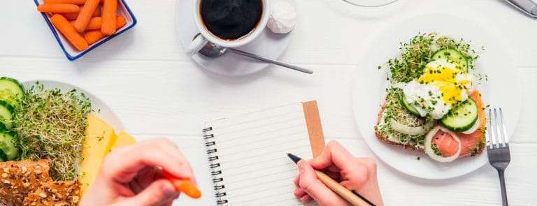 Notebook on a white table surrounded by an array of foods