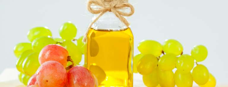 bottle of grapeseed oil next to fresh grapes