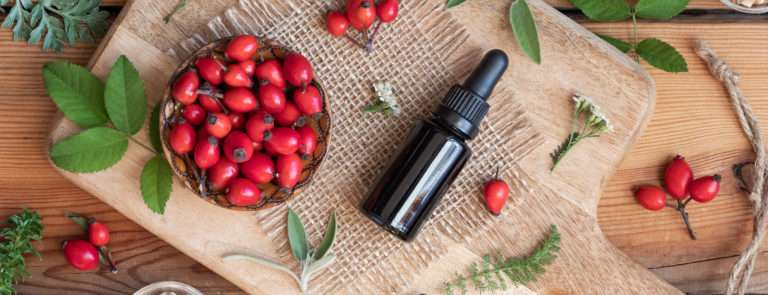 a bottle of rosehip oil and rosehips