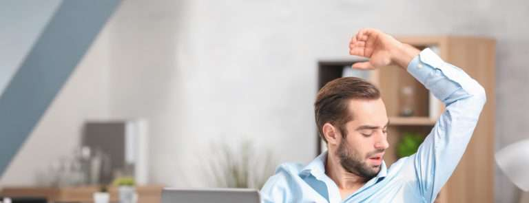 man in office with a sweat under his armpit