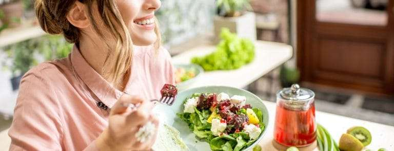 Young woman eating healthy food sitting in the beautiful interior with green flowers on the background