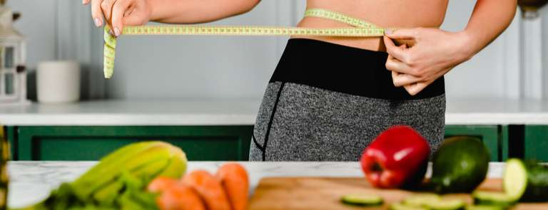 woman measuring waist with healthy foods in foreground
