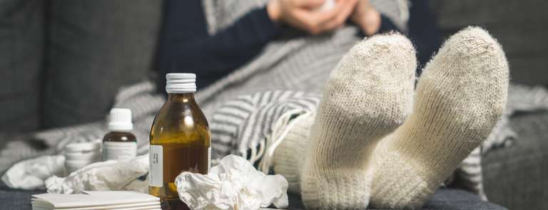 sick person with flu next to tissues and medicine bottles