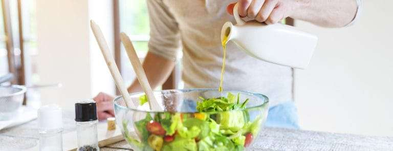 Man drizzling olive oil over a bowl of salad