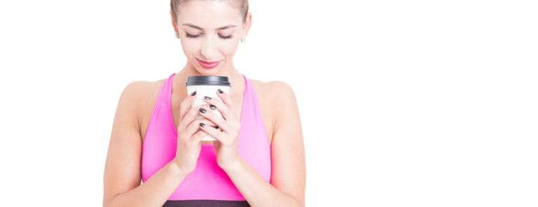 A women in gym clothing holding a cup of coffee
