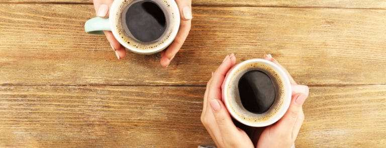Two cups of coffee on a wooden table being held by two women