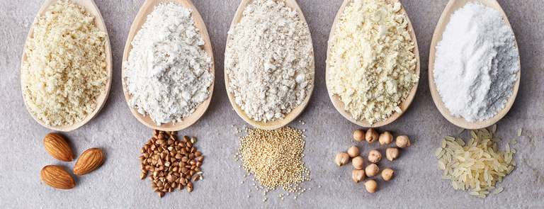 different kinds of gluten free flour in wooden spoons