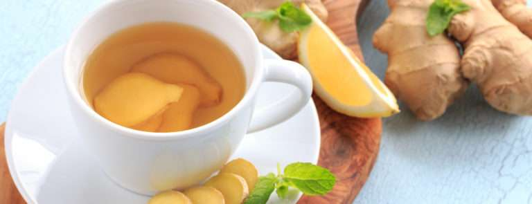 A chopping board with a cup and saucer with chopped ginger on. The cup has ginger tea in with ginger and lemon scattered around the chopping board.