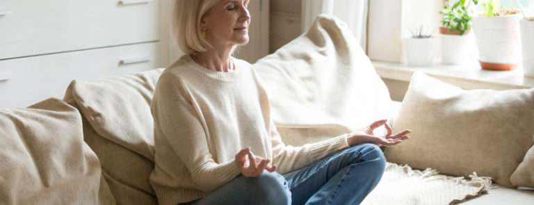 Woman medidating in her home due to self isolation