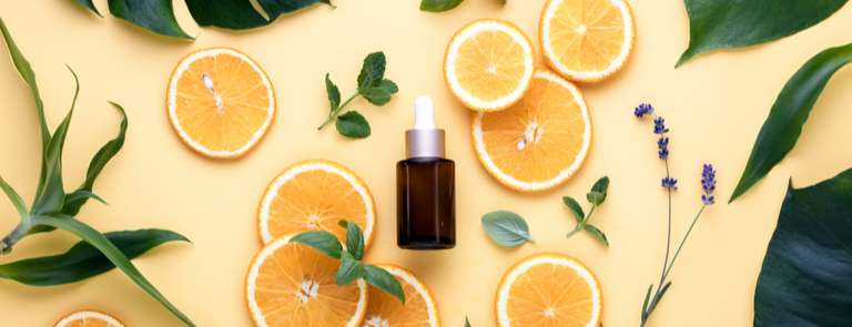 essential oil bottle with orange slices and leaves
