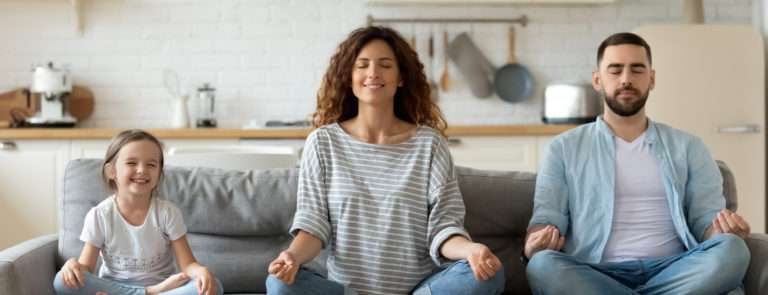 A man, woman and child sitting on a sofa in a yoga position with their eyes closed.