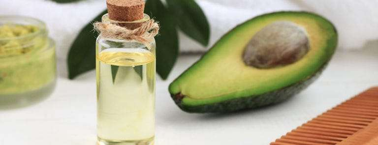 A white hair towel with half an avocado, a wooden comb and a bottle of hair oil