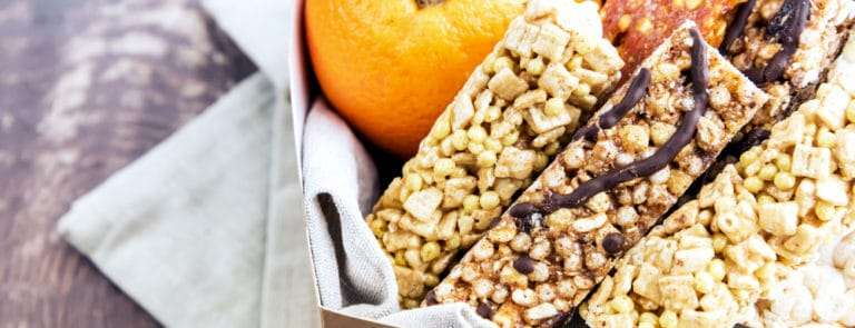 Box with Variety of muesli bars and fruit Granola bars grapes orange Healthy food for breakfast