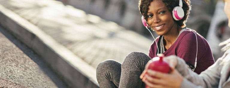 A Women Sat On A Pavement Listening to Music on Headphones